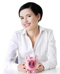 Happy businesswoman holding piggy bank
