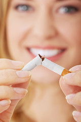 Young beautiful woman holding broken cigarette
