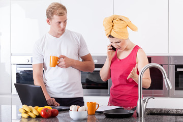 Busy couple in the morning in kitchen