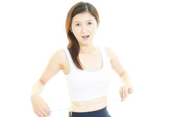 腹囲を測定する笑顔の女性