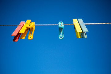 Colored clothespins with blue sky