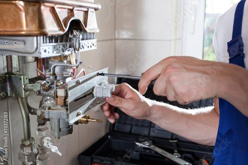 Handyman adjusting gas water heater - 70372183