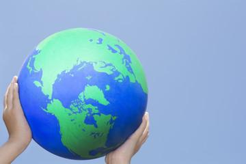手に持った地球の模型と青空