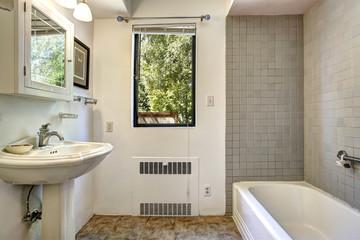 Old bathroom with grey tile wall trim
