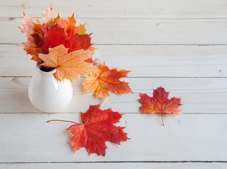 Autumn maple leaves bunch in vase on old wooden background