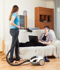 Girl cleaning at home while man with laptop