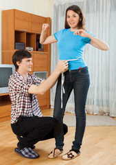 Man measuring girlriend waist with measuring tape
