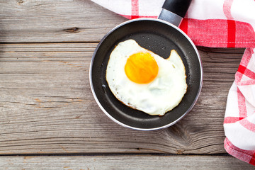 Fried egg in a frying pan, on an old wooden table