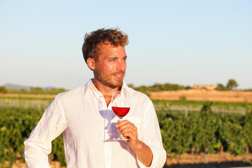 Winemaker man drinking rose or red wine, vineyard
