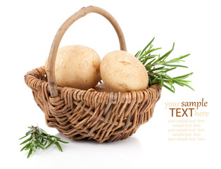 Golden Potatoes in wicker basket, with rosemary over white backg