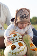 Baby in arms playing with pumpkins