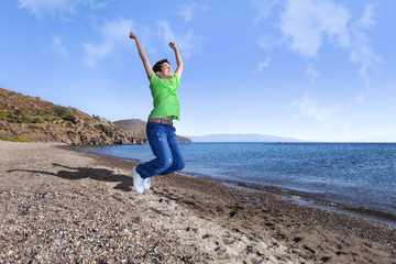 Happy young boy is jumping at the sea side