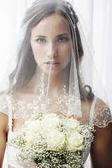 Serious young bride in veil holding bouquet.