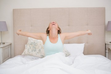 Happy blonde waking up in bed