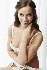 Sexy young bride in lingerie looking at camera.