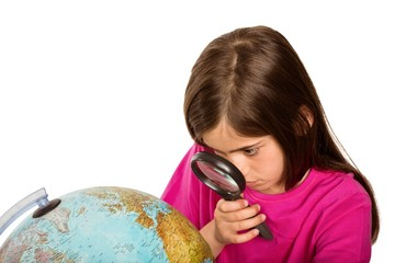 Cute pupil looking at globe through magnifying glass