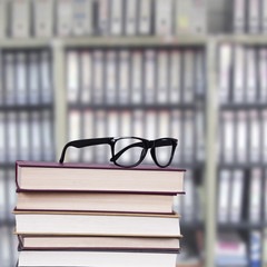 glasses above the stacked books, business and objects