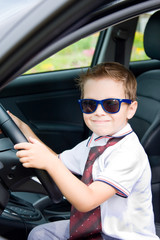 Boy with glasses and tie sitting in car
