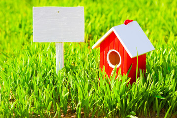 Red house and signboard on grass
