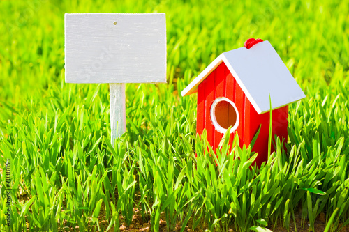 Leinwanddruck Bild Red house and signboard on grass