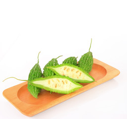 Bitter melon or bitter gourd in wooden plate on white