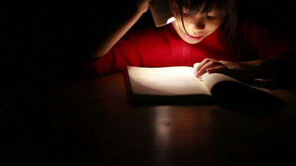 Dolly Cute Asian girl reading book in darkness, with flashlig