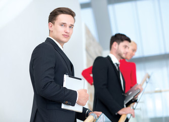 Portrait of motivated and handsome businessman with collegues on