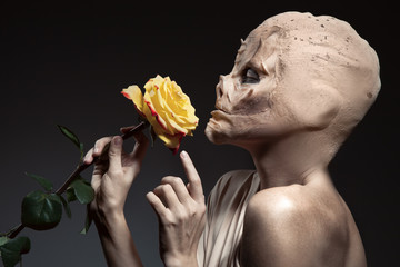 Beauty and the beast. Ugly witch with beautiful flower in hand.