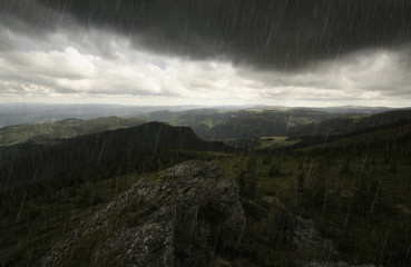 mountain landscape during a storm with rain and dark clouds