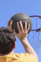 Detail of basket-ball player on a daylight sky.