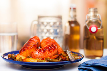 grilled sausages with tomato, potatoes and green beans