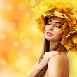 Beautiful young woman with yellow autumn wreath
