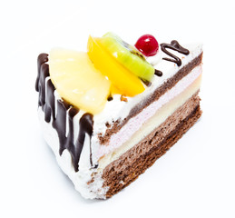 Piece of chocolate cake with icing and fresh fruit isolated