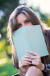 Young woman hiding behind a book in the park.