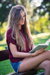 Young woman reading a book sit on a bench in the park.