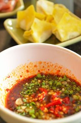 Spicy dipping sauce with dumpling background