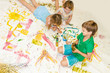 three kids painting over white