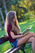 Young woman reading a book sit on a bench in the park. Filtered