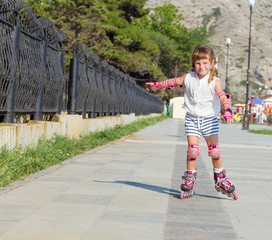 cute happy child girl roller skating on natural background