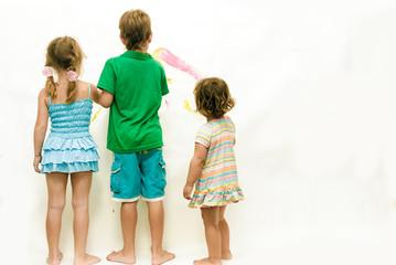 three kids painting over white