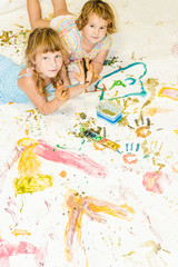 two cute young child girls painting over white