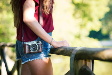 Young woman with vintage camera detail outdoors in a park.