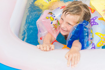 young happy child girl swimming in pool with swimming ring