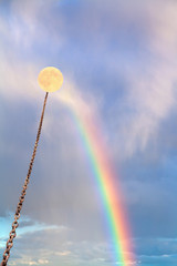 full moon tied on chain soars on rainbow
