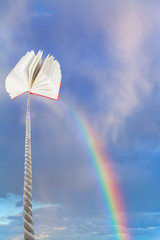 book tied on cord soars into sky with rainbow