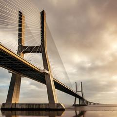 Vasco da Gama Bridge over the Tagus river at sunrise with cloudy