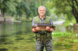 Mature fisherman standing in river and holding fish