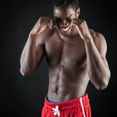 Strong young black man shirtless portrait against black backgrou