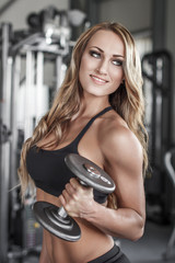 Female fitness model posing with dumbbell