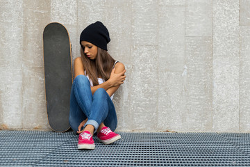 Teenager with skateboard portrait sit against concrete wall.